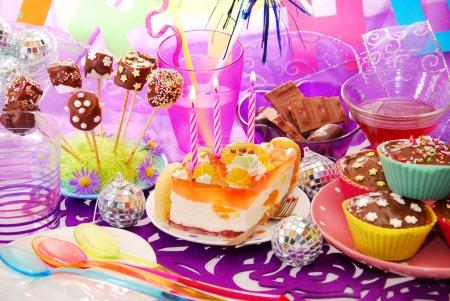 Foto de Colorida decoración de mesa de fiesta cumpleaños con torta y dulces para niños - Imagen libre de derechos