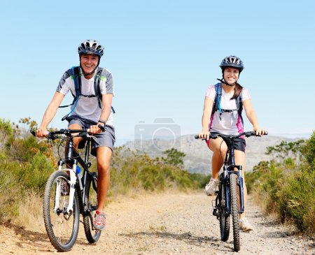 Photo for Happy carefree mountain bike couple cycling outdoors and leading a healthy lifestyle. - Royalty Free Image
