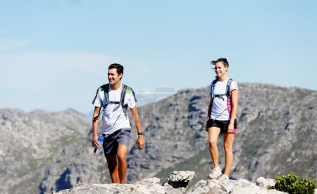 Photo for Young couple hiking outdoors in the sunshine, healthy lifestyle concept - Royalty Free Image