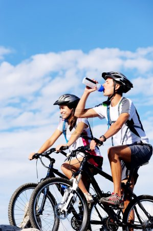 Photo for Cyclist drinking water to ensure hydration and to quench thirst. - Royalty Free Image