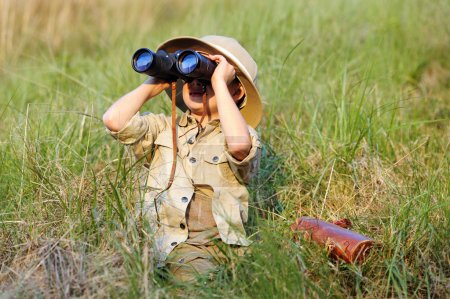 Photo for Young boy child playing pretend explorer adventure safari game outdoors with binoculars and bush hat - Royalty Free Image
