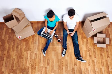 Photo for Overhead view of couple sitting on floor together using computer wireless internet while moving into new home - Royalty Free Image