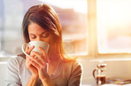 Photo for Woman drinking coffee at home with sunrise streaming in through window and creating flare into the lens. - Royalty Free Image