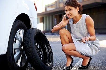 Photo pour Femme appelant à l'aide avec pneu à plat sur la voiture dans la ville - image libre de droit