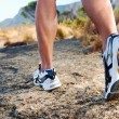 Trail running athlete feet on rock excercising fit...
