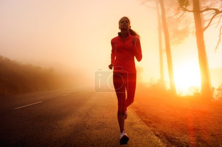 Photo for Healthy running runner woman early morning sunrise workout on misty mountain road workout jog. sunflare through the mist gives atmospheric feel and depth to these fitness images - Royalty Free Image