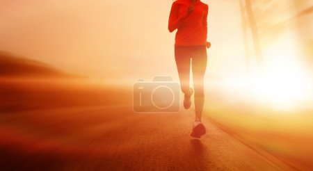 Athlete running on the road in morning sunrise tra...