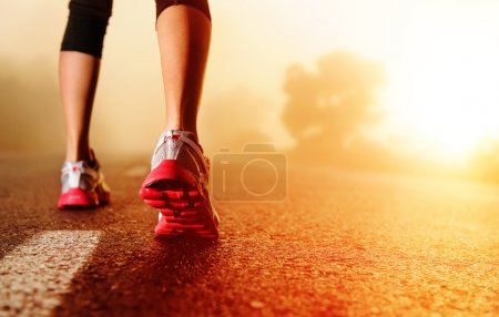 Photo for Athlete runner feet running on road closeup on shoe. woman fitness sunrise jog workout concept. - Royalty Free Image