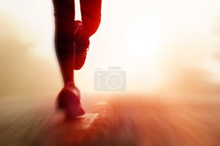 Photo for Runner athlete feet running on road. woman fitness silhouette sunrise jog workout welness concept. with motion blur - Royalty Free Image