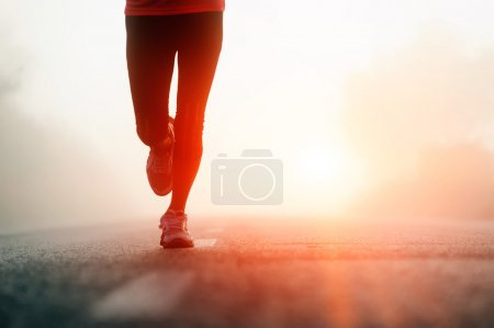 Photo for Runner athlete feet running on road. woman fitness silhouette sunrise jog workout wellness concept. - Royalty Free Image