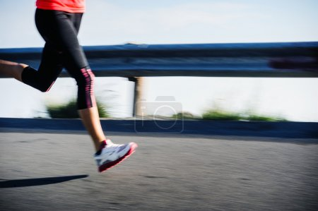 Photo for Athlete runner motion blur running on road focus on shoe. woman speed sprint fitness training. - Royalty Free Image