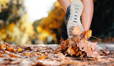 Photo for Close up of feet of a runner running in autumn leaves training for marathon and fitness healthty lifestyle - Royalty Free Image