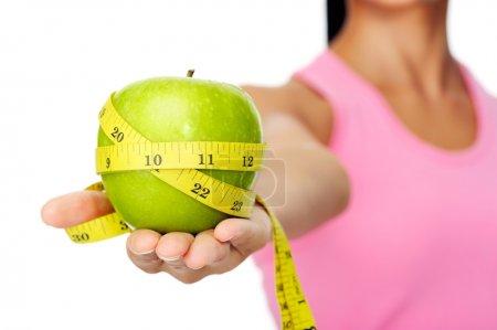 Photo pour Femme hispanique heureuse en bonne santé avec apple et ruban à mesurer pour la notion de perte de régime alimentaire et le poids - image libre de droit