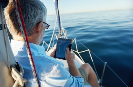Photo for Sailing man reading tablet computer on boat with modern technology and carefree retired senior successful lifestyle - Royalty Free Image