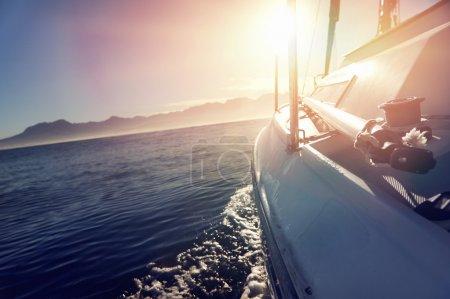 Photo pour Bateau à voile sur l'eau de l'océan au lever du soleil avec fusée éclairante et style de vie en plein air - image libre de droit
