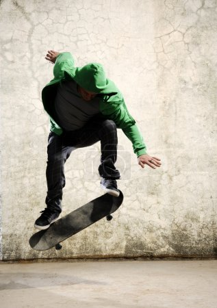 Photo for Skateboarder doing trick in mid air, grunge background - Royalty Free Image