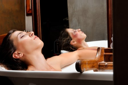 Photo for Woman relaxing in bathtub with mirror image of her with bruises on her face, a conceptual shoot of domestic abuse often hidden from public - Royalty Free Image