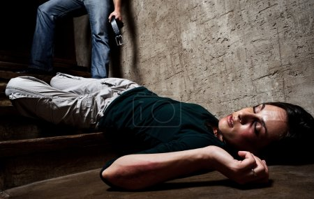Photo for Battered woman lies lifelessly at the bottom of stairs with a faceless man holding a belt, a conceptual shoot portraying the process and effects of domestic violence - Royalty Free Image
