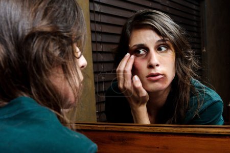 Photo for Battered woman checks the extent of her injuries in the bathroom mirror - Royalty Free Image