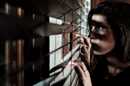 Photo for Fearful battered woman peeking through the blinds to see if her husband is home - Royalty Free Image