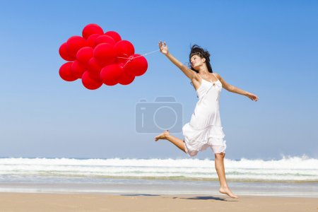 Photo for Beautiful girl walking in the beach and holding red balloons - Royalty Free Image