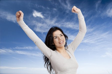 Photo for Happy young woman with arms up agains a blue sky - Royalty Free Image