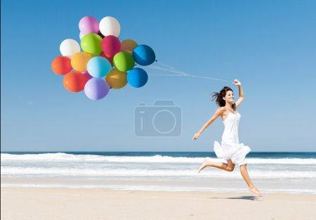 Photo for Beautiful girl walking in the beach while holding colored balloons - Royalty Free Image