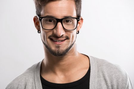 Photo for Portrait of a handsome young man wearing glasses, over a gray background - Royalty Free Image