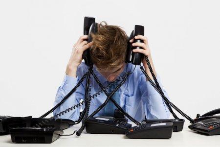 Foto de Hombre joven en la oficina y responder a varios teléfonos al mismo tiempo - Imagen libre de derechos