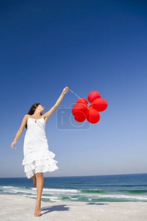 Photo for Beautiful girl jumping with red ballons in the beach - Royalty Free Image