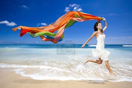 Photo for Beautiful woman running and jumping in the beach with a colored tisue - Royalty Free Image