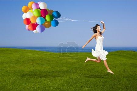 Photo pour Belle femme courant et sautant sur une prairie verte avec des ballons colorés - image libre de droit