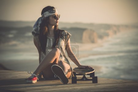 Beautiful young woman sitting over a skateboard...