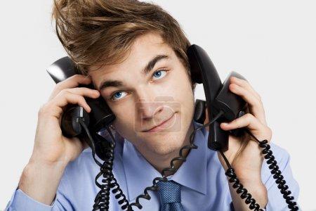 Foto de Joven sentado en la oficina y responder a varios teléfonos al mismo tiempo - Imagen libre de derechos