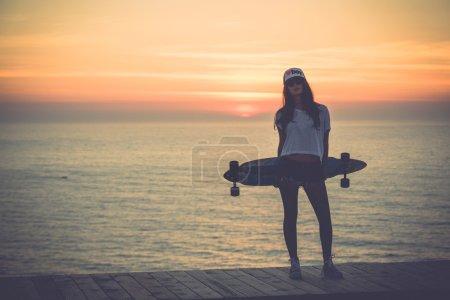 Foto de Hermosa y joven posando en la puesta del sol con un patín de moda - archivo un poco ruidoso - Imagen libre de derechos