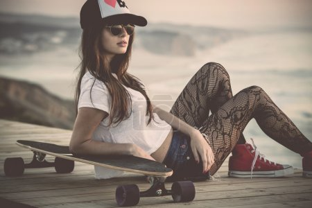 Photo for Beautiful and fashion young woman posing with a skateboard - Royalty Free Image