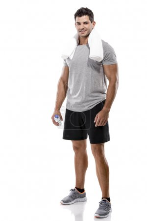 Photo for Portrait of a athletic man after doing exercises and holding a bottle of water, isolated over a white background - Royalty Free Image