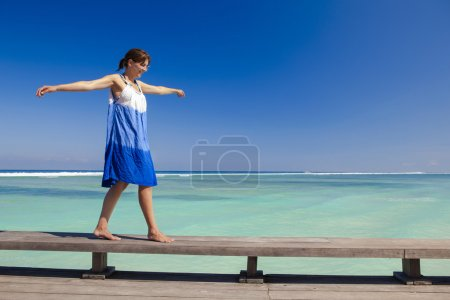 Photo for Beautiful woman walking with arms open on a beautiful tropical beach - Royalty Free Image