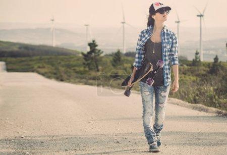 Photo pour Belle jeune femme marchant et tenant une planche à roulettes - image libre de droit