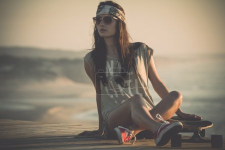 Photo for Beautiful young woman sitting over a skateboard - Royalty Free Image