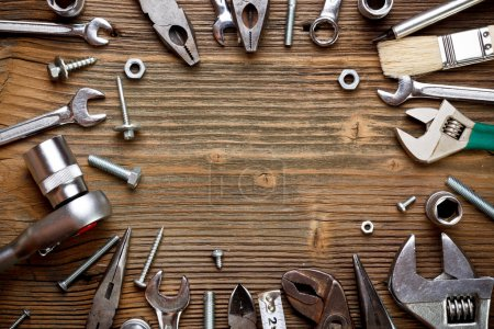 Group of used tools on wood background...