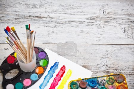 Photo for Box of watercolors and paintbrushes on wooden desk - Royalty Free Image