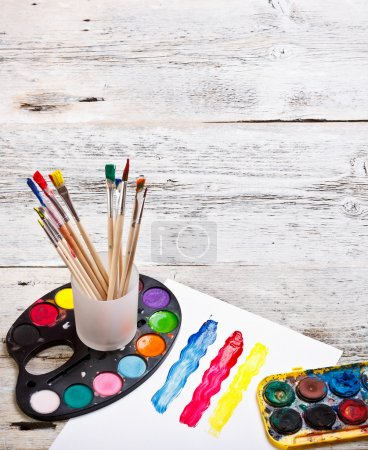 Photo for Paints and brushes on a wooden background - Royalty Free Image