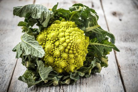 One whole Romanesco broccoli on wooden background...
