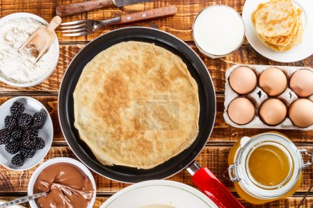 Frying pan with pancake and pancake ingredients...