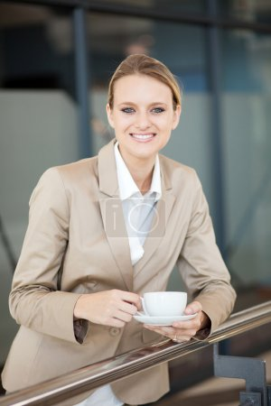 Beautiful female white collar worker having coffee break at work