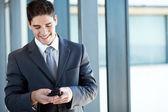 Heureux homme d'affaires, lecture des emails depuis un téléphone intelligent