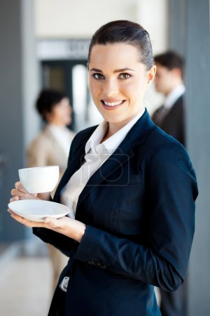 Beautiful young businesswoman drinking coffee in o...