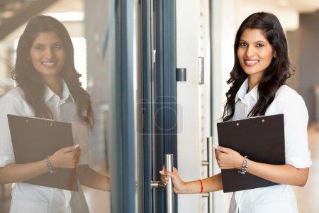 Indian white collar worker opening office door