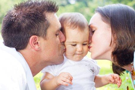Photo pour Parents baiser la petite fille à l'extérieur - image libre de droit